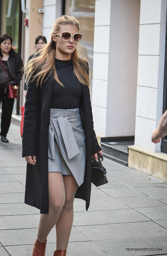 Peopleandstyles. What to wear. Culottes. This street stunner styled well her wrap mini skirt and ankle boots keeping the look elegant with a black clean line coat and a black bodysuit. 70s sunglasses